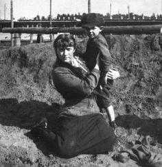 """Grã-duquesa Anastasia Nikolaevna da Rússia abraça o menino """"Lenka"""" em uma estação de trem próximo à Mogilev. O trem Imperial fica no fundo. Primavera de 1916."""