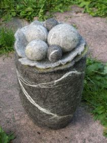 een urn die met wol en vilten persoonlijk is gemaakt en een warme uitstraling heeft gekregen