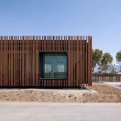 These photographs by Julien Lanoo show a French driving-test centre by Samuel Delmas Architectes, which is camouflaged to look like a fence. Weathered rods of Corten steel surround the exterior of the Centre d'Examen du Permis, interrupted by black-framed box windows. This screen provides solar shading for the glazed, prefabricated building while fences in the