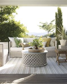 This patio is a summer getaway. The neutral color scheme is brightened with natural decor and a pop of color. The juxtaposition of a round coffee table on a striped rug is eye-catching.