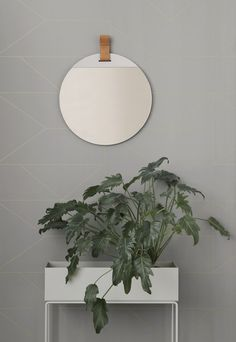 Round mirrors are the perfect way to add a point of interest to your hallway. We love this Fern Living leather strap mirror from Trouva, click now to explore more.