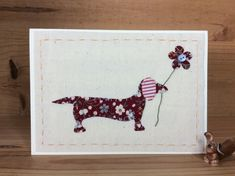 Dora Dachshund card is completely hand-stitched with retro style floral fabrics and is holding a flower in her mouth. She is stitched onto a calico background and backed onto cream card. This one of a kind card is left blank inside for your own wording. Fabric Cards, Fabric Postcards, Card Patterns, Floral Fabric, Hand Stitching, I Card, Dachshund, Gift Guide, Birthday Cards