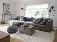 Gray linen sectional, grey pouf, wooden trunk as table