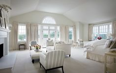 Large master suite with vaulted ceiling, French doors, transom windows, tan walls paint color, fireplace, white sofa, white ottoman, striped accent chairs.