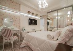 Para o quarto da menina, a ideia foi imprimir um delicado ar romântico. O mobiliário, todo em laca branca, integra peças projetadas pelas arquitetas e outras soltas, no estilo provençal. Revestimentos e acabamentos em tons de rosa, como na cabeceira da cama e o papel de parede, completam a proposta.