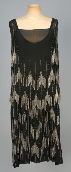 ADAIR PARIS CHIFFON FLAPPER DRESS with BEADED FRINGE, 1920s. Black silk with crystal fringe forming an allover scallop pattern with vertical bands of clear and silver beads, blouson top and chiffon underdress. Labeled. B-40, L-42. (Tear under one arm, bead losses) good.