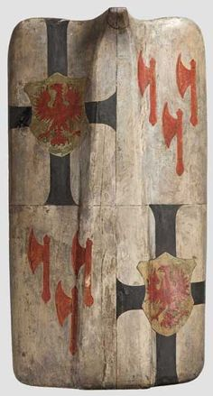 A pavise, historicism in the style of circa 1480 The lime wood shield carved in one piece, with a pronounced medial rib. The front gessoed and painted with a coat of arms in colour. The back covered in old, handwritten vellum. The shield grip made of an ox penis. The edges knocked in places, a small defect in the vellum covering on the back. Outstanding 19th century workmanship. Dimensions 83 x 47 cm. Hermann Historica 70. Auction 04./05.2015 Lot Nr. 3204