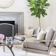 Alyssa Rosenheck - Amanda Barnes Interior Design - Elegant living room features a round ivory mirror placed above a gray glossy fireplace accented with silver tiles placed next to a fiddle leaf fig plant. Zen Living Rooms, Modern Farmhouse Living Room Decor, Elegant Living Room, Living Room Designs, Cozy Living, Modern Living, Mantel Styling, Amanda Barnes, Style Me Pretty Living