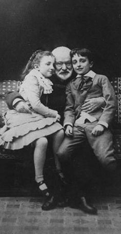 Victor Hugo was born February 26, 1802, in Besancon, France and died in Paris, 1885. Pictured here with his grandchildren, Georges and Jeanne Hugo. He wrote Les Misérables and The Hunchback of Notre Dame.