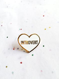Introvert heart hard enamel lapel pin. Smooth white hard enamel with gold trim. Comes with a soft rubber pin back. Pin this to your favorite