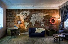 décoration murale industrielle, brique de parement rouge, sol en parquet et canapé bleu marine