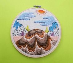 Hand stitched embroidery of a bizarre landscape of a melting mountain surrounded by other fantastical elements. Made with DMC embroidery floss in a 8 inch bamboo hoop, which serves as a frame. Perfect