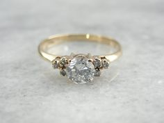 This is a classic ring for a lady who wants a little more oomph than just a traditional solitaire. Set with bright diamonds on the sides, this half carat stone has plenty of life and light!    Metal: 14 Karat Yellow Gold Center Diamond: .50 carat,, Round Cut, E Color, I1 Clarity, Side Stones: 6 diamonds weighing .06 carats  Size of Ring: 5.25, but can be sized to fit almost any finger (please see our sizing policies).  SKU:JUDPKQ-P    For questions about diamond grading, we recommend the…