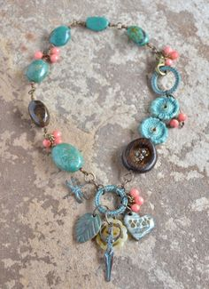 https://flic.kr/p/u8k3it | nayeli by ruby acorn | nayeli by ruby acorn  as seen in the summer 2015 issue of Stringing Magazine  ceramic leaf - Kylie Parry  ceramic heart - Elaine Ray  ceramic discs - Marsha Neal Studio  lampwork glass teardrops - Unicorne Beads  mykonos rings, mykonos dragonfly, mykonos goddess, jade flower, turquoise nuggets, bronzite nugget, coral shell faceted rounds, Vintaj, waxed Irish linen cord