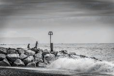 An eye-catching black and white image of children on a rocky beach, looking out at the water, with noisy, aggressive waves crashing all around them. Friends share so many memories, and such days in the outdoors build lifelong relationships. This image is an ode to such childhood bonds