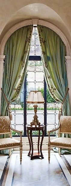 arched window with leaded glass framed by drapery styling