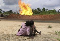 Kinderen aanschouwen een gasfakkel. In de Nigerdelta wordt het gas dat bij de oliewinning vrijkomt in brand gestoken, met andere woorden afgefakkeld. De fakkels branden dag en nacht. Foto Elaine Gilligan.