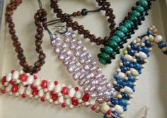 Woven bead bracelets -- wooden beads )the brown, the red and white, the blue and the green and black) and one of pearls.