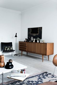 Chandler and Joey's bachelor pad reimagined with a midcentury feel, a vintage console, and leather chairs