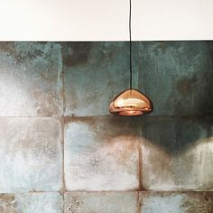 The oxidized brass finish of these Trace by Caesar tiles brings patina and dimensionality to this backsplash.