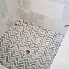 Amazing shower features a marble surround alongside a white and gray marble herringbone shower floor.