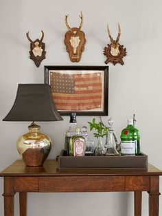 The American flag is a circa-1915 find from the Brimfield Antique Show; the Parsons desk, mercury-glass lamp, and hunting trophies are all vintage.