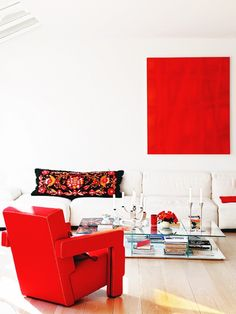 Living room with white sofa and red accent armchair, pillow, and art, as well as a glass coffee table.