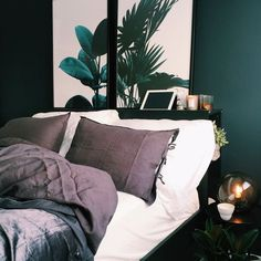 Bringing nature inside has been a trend for while and this is a great example featuring dark green walls, botanical prints, and accented with the dusky purple bedding⁠