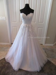 Description Feminine lace and tulle ballgown with a ornate late fitted bodice. Featured a sweetheart neckline with a scalloped lace detailing. The lace then cascades down the top of the layered tulle