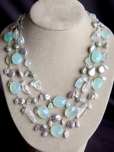 "Harmony's Galene Necklace is a chunky, elegant, and stunning piece. Large, smooth gems of sea-foam green Chalcedony alternate with chunky, raw cut Aquamarine and silver coin pearls. Dangling are silver keshi pearls, adding even more luster and movement. As one of our customers said ""it looks like water in color and movement."" Harmony's Galene Multi Strand necklace is very limited edition, with four each available in sterling silver and 22kt gold vermeil. The short measures 16-18"", while…"