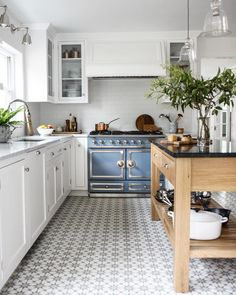 A white refreshing kitchen space featuring a french blue stove and jazzy patterned tile floor