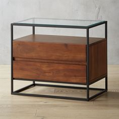 Shop Crawford Glass Top Nightstand. Boxy black iron frame holds two floating solid acacia wood drawers and tops off in clear glass. Best of both storage worlds, open shelf nightstand displays current reads while drawers hold TV remotes and phone chargers. CB2 exclusive.