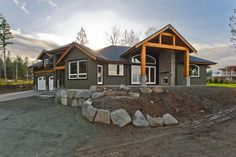 Dark grey siding with cedar beams and accents, grey rock outdoor fireplace
