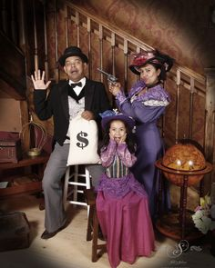 Little girl shocked at her mom holder her dad up for his money bag!  They are dressed in old west fancy attire and standing in front of our stair case set.  #fun #familyfun #familyphotos #oldtimestyle #oldtimephotos #oldtymephotos #photography #dressup #glenwood #glenwoodsprings #glenwoodcaverns #glenwoodcavernsadventurepark #thingstodo #thingstodoincolorado #thingstodocolorado #colorado #coloradovaca #coloradovacation