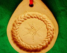 ELSA Frozen Snowflake Cookie Mold doubles as Ornament.  Holiday Design in Food Safe Stoneware. A Braid Borders the Snowflake  in the Center.