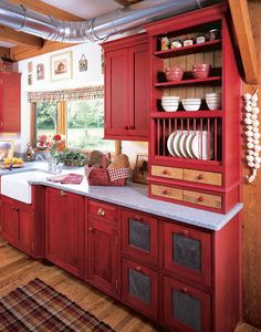 Red cabinetry, especially if it's stained rather than painted, can give a kitchen a warm, traditional country feel. It goes well with the the warm tones of the natural wood too.