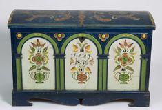 Kiste med buet lokk og fotstykke. Lokket er rosemalt og forsiden har tre buer med rosemalte fyllinger.