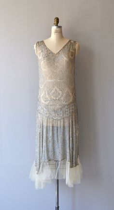 Otherworldy vintage 1920s silk dress entirely covered in silvery beading with subtle teardrop pattern, identical from back to front with V neckline, classic 1920s shape and airy tulle trimmed hem. --- M E A S U R E M E N T S --- fits like: medium/large bust: 34-38 waist: up to 36 hip: up to 45 length: 49 brand/maker: n/a condition: some missing beading at one shoulder, not a hole in the fabric. ✩ layaway is available for this item To ensure a good fit, please read the sizing guide…