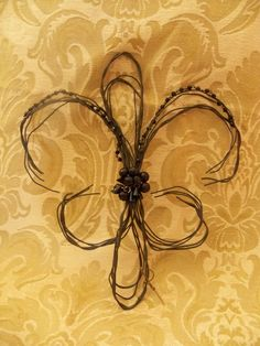 Fleur di lis. I'd like this with a little more substance. Maybe done in barbed wire?