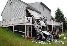 A tow truck operator tries to figure out how to tow a Jeep  after the driver drove through the back wall of his own garage, falling one storey to the ground, in Lancaster, Pennsylvania. The driver said that as he was returning home, the vehicle's accelerator stuck and he couldn't stop before hitting the house. The driver was not hurt.