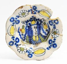 A SMALL LATE 17TH CENTURY MOULDED DUTCH DELFTWARE DISH, painted in blue, yellow and green with a portrait of King William III and with 'WR' above, within a floral border and marked 'noii' to the reverse, 15.8cm diameter