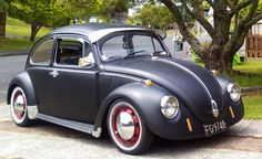 1970 VW Beetle. Flat black, red rims, chrome, with visor