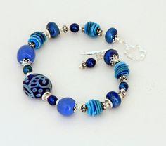 Beautiful scroll focal bead by Kaye Husko. Lovely blue fiber beads by Jana Severin. Bracelet by Wild Woman Beads.