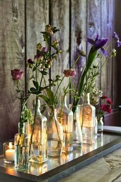 Single stems in small bottles with tea lights set behind them -- on a mirror on table!Decoracion vintage.