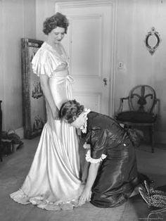 Mrs. Elizabeth Arden Graham Having Her Maid Fix Hem of Evening Gown