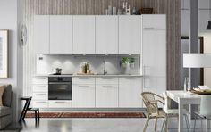 Kjøkken med moderne hvit design, RÅSDAL fronter i hvit ask, hvite benkeplater og innebygde hvitevarer