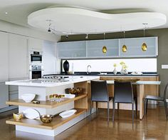 From the Ceiling on Down The crown of this kitchen, an amoeba-shaped ceiling soffit, is only the beginning fun and funky characteristic in this kitchen. The L-shape island showcases collectibles on open shelves and also serves as prep and eating areas. Amber-colored pendant lights coordinate with the honey-hued Italian walnut cabinets.