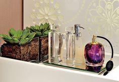 """Duas suculentas em caixas de vidro provam que até no lavabo é possível ter plantas. Na bancada, elas dividem a área com perfumeiros. """"Primeiro são colocadas as cascas de pínus e, no centro delas, a suculenta com um pouco de terra e areia"""", explica a paisagista Drica Diogo"""