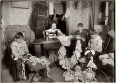 "March 1912. ""Making dresses for Campbell Kid Dolls in a dirty tenement room, 59 Thompson Street, New York, 4th floor front. Romana family. The older boy, about 12 years old, operates the machine when the mother is not using it, and when she operates, he helps the little ones, 5 and 7 years old, break the thread."" Photo and caption by Lewis Wickes Hine."