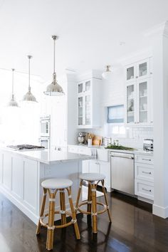 Gorgeous white kitchen features white shaker cabinets paired with white marble countertops and a white beveled subway tile backsplash. Kitchen Island Corbels, Narrow Kitchen, White Beveled Subway Tile, White Marble, Style Me Pretty Living, White Shaker Cabinets, All White Kitchen, Crisp Kitchen, Cuisines Design